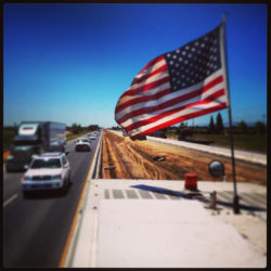 american flag on top of anrak truck
